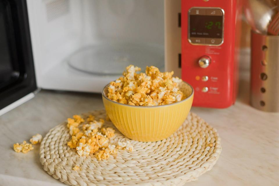 Popcorn is taken out of the microwave in the kitchen.