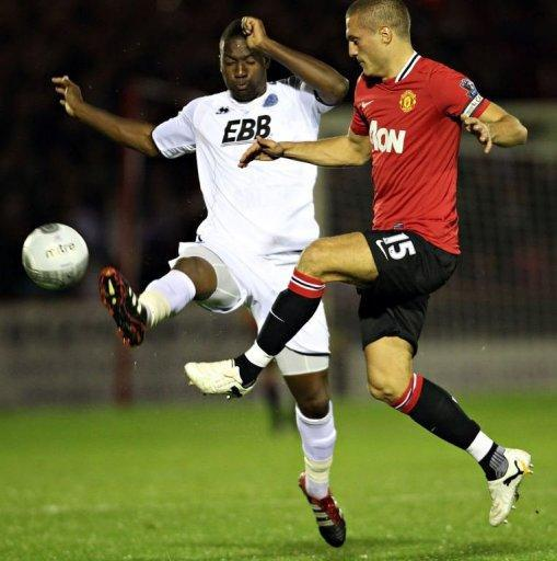 Manchester United's Serbian player Nemanja Vidic (R) vies for the ball against Aldershot Town's Michael Rankine (L) during the Carling Cup fourth round football match between Aldershot Town and Manchester United at The Recreation Ground in Aldershot. United won 3-0