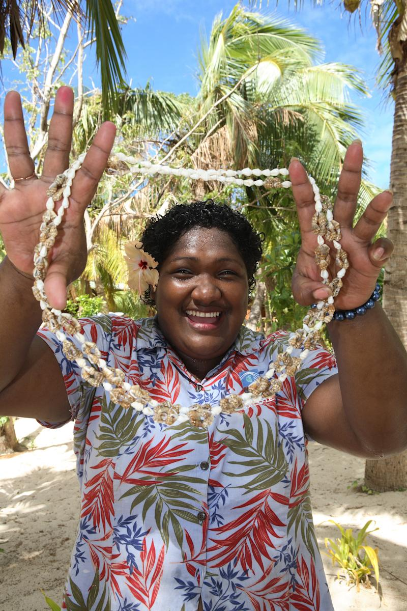 A smiling happy Fijian woman welcomes you to Fiji with a necklace of seashells