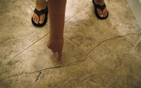Mary Mahan points to a crack in the floor tile of her home that she said was a result of an earthquake in Wooster, Arkansas in this file photo taken August 5, 2013. REUTERS/Jim Young/Files