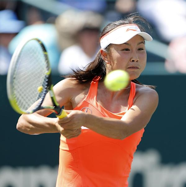 Peng Shuai, of China, returns to Sara Errani, of Italy, during the Family Circle Cup tennis tournament in Charleston, S.C., Thursday, April 3, 2014. (AP Photo/Mic Smith)