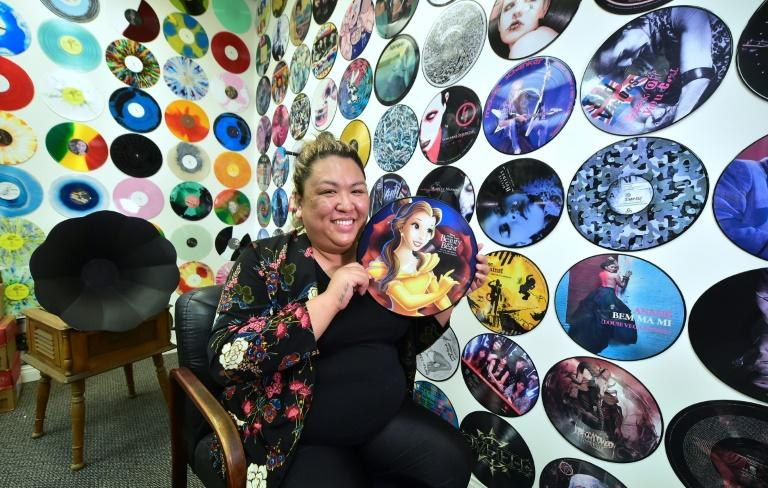 "Ma Nerriza dela Cerna of Erika Records displays a full color ""Beauty and the Beast"" record at the company's office in Buena Park, California on April 12, 2017, where the record manufacturing business has been pressing vinyl for over 30 years"