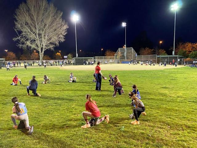 Players on the U.S. Olympic softball team instruct youth players during a clinic it hosted at Santee, California
