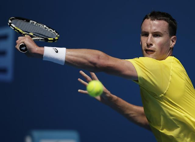 Kenny De Schepper of France makes a backhand return to Tomas Berdych of the Czech Republic during their second round match at the Australian Open tennis championship in Melbourne, Australia, Wednesday, Jan. 15, 2014.(AP Photo/Rick Rycroft)