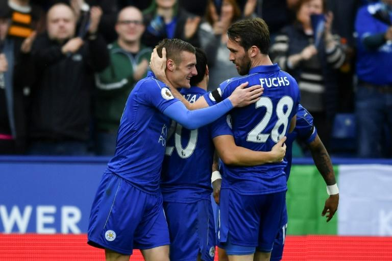 Leicester City's Jamie Vardy (L) is congratulated by teammate Christian Fuchs after scoring a goal during their English Premier League match against Stoke City, at King Power Stadium in Leicester, on April 1, 2017