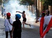 A demonstrator throws a stone during a protest in Beirut