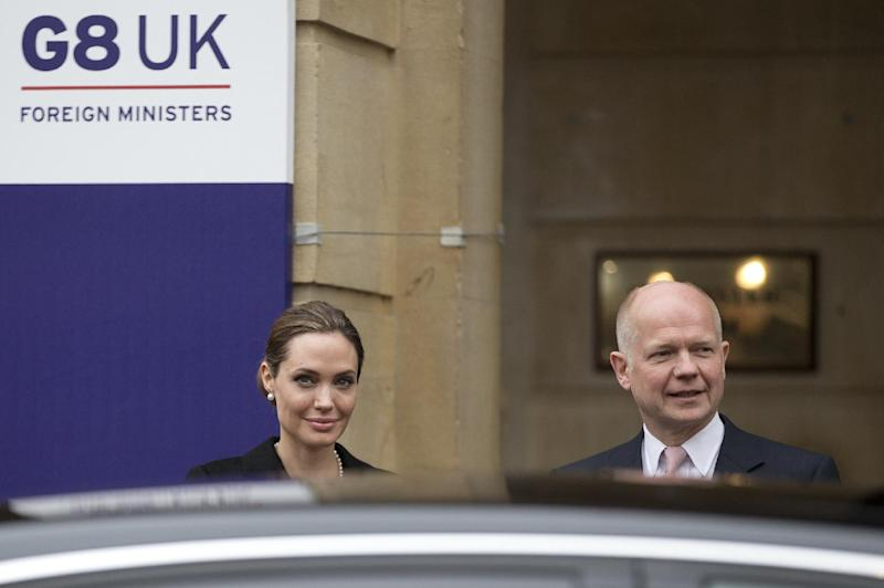 Angelina Jolie  stands with Britain's Foreign Secretary William Hague as she  arrives for the start of a G8 Foreign Ministers meeting in London, Thursday, April, 11, 2013. The ministers are meeting in London as Britain currently holds the G8 Presidency, with the heads of government G8 meeting set for June in Northern Ireland.(AP Photo/Alastair Grant)