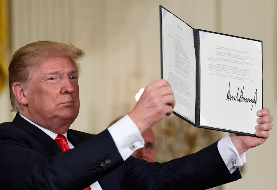 President Trump holds up the space policy directive that he signed during a National Space Council meeting in the East Room of the White House in Washington. (AP Photo/Susan Walsh)