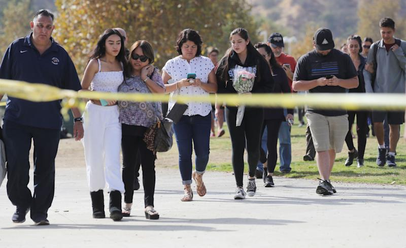 Students and family members walk after being reunited at a park near Saugus High School after the shooting. Source: Getty