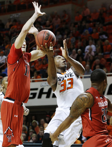 Oklahoma State guard Marcus Smart (33) shoots between Texas Tech forward Dejan Kravic (11) and guard Toddrick Gotcher (20) during the second half of an NCAA college basketball game in Stillwater, Okla., Saturday, Feb. 22, 2014. Oklahoma State won 84-62. (AP Photo/Sue Ogrocki)