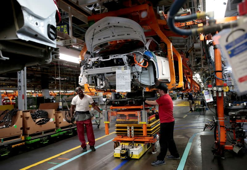 FILE PHOTO: General Motors assembly workers connect a battery pack underneath a partially assembled Chevrolet Bolt EV vehicle