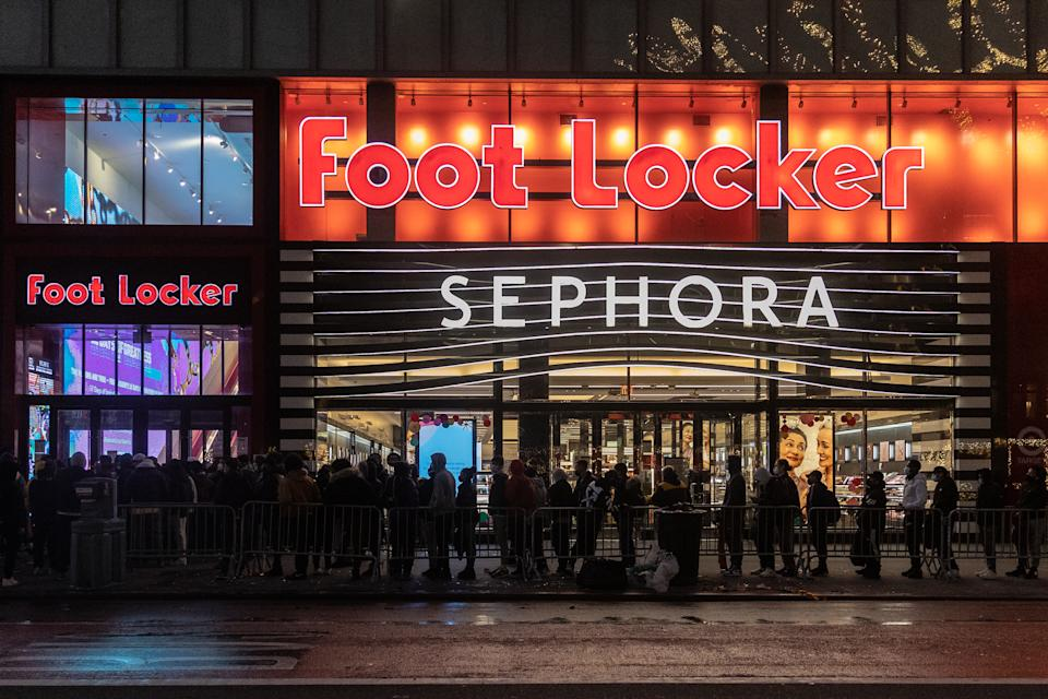 NEW YORK, NY - NOVEMBER 27: People wearing protective masks wait in line to enter Foot Locker store during Black Friday on November 27, 2020 in New York, United States. Shoppers go out early despite ongoing concerns and limitations due to COVID-19 this year. (Photo by Jeenah Moon/Getty Images)
