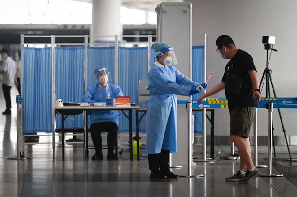 An airport worker wearing protective clothing takes a temperature reading of a man at the Beijing International Airport.