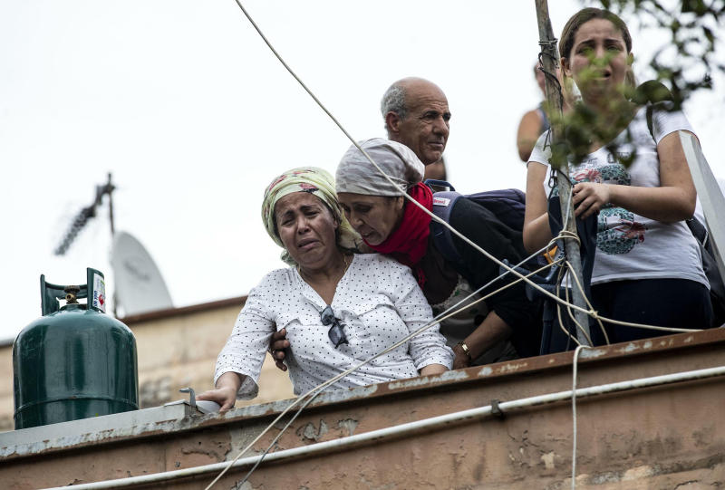 A woman cries as she stands with others on the roof of an abandoned school before being evicted, on the outskirts of Rome, Monday, July 15, 2019. Residents set fire early Monday to mattresses and other garbage to form a barrier and prevent riot police from entering the building but authorities doused the blaze and proceeded with the eviction. (Massimo Percossi/ANSA via AP)