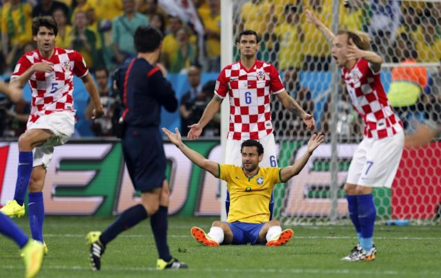 Brazil's Fred sits on the pitch as Croatian players Vedran Corluka (5), Dejan Lovren (6) and Ivan Rakitic (7) protest after referee Yuichi Nishimura, from Japan, called a penalty against Croatia during the group A World Cup soccer match in the opening game of the tournament at Itaquerao Stadium in Sao Paulo, Brazil, Thursday, June 12, 2014. Brazil's Neymar scored on a penalty kick after the play. (AP Photo/Frank Augstein)