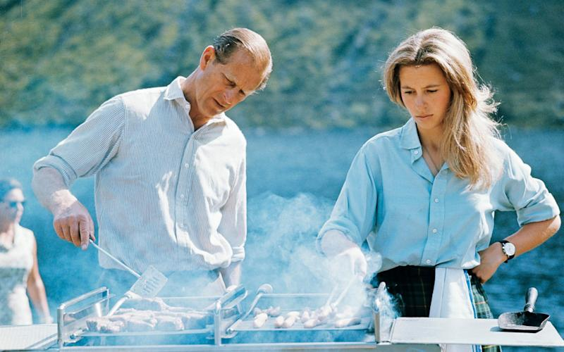 The Duke of Edinburgh and Princess Anne preparing a barbecue on the Estate at Balmoral Castle in 1972 - Credit: Lichfield/Getty Images