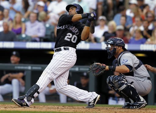 Colorado Rockies' Wilin Rosario follows through on a solo home run as San Diego Padres catcher Yasmani Grandal watches during the third fifth inning of the Padres' 8-4 victory in a baseball game in Denver on Saturday, June 30, 2012. (AP Photo/David Zalubowski)