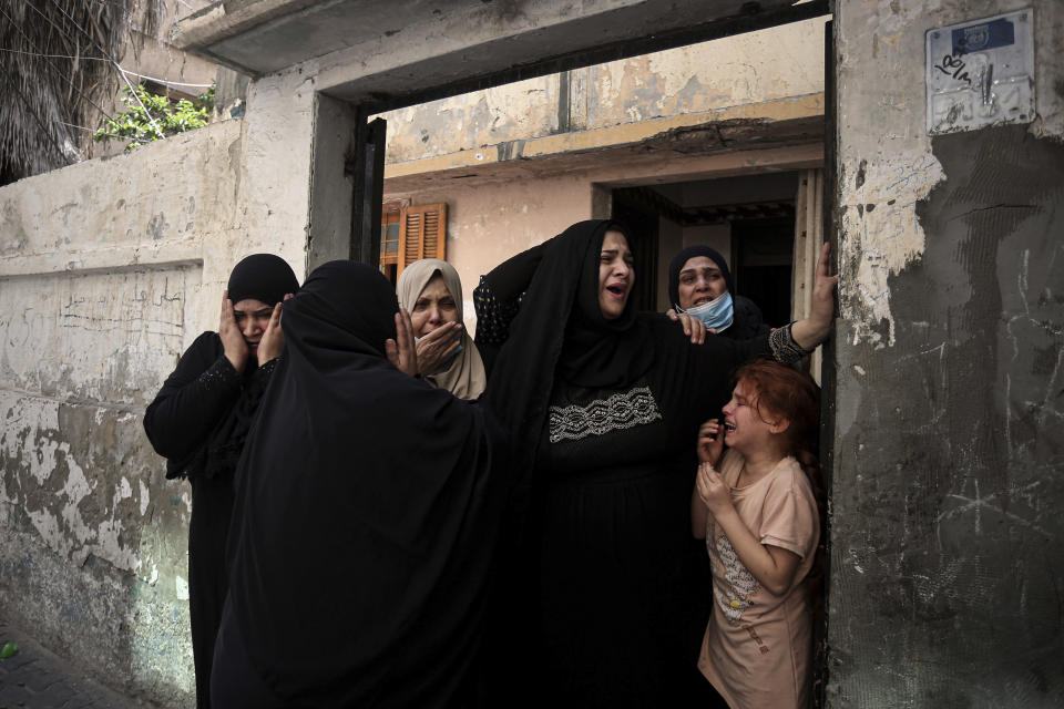 Relatives of Hoda Al-Khozondar, who was killed in an Israeli airstrike, react as mourners carry her body out of the family home, during her funeral in town of Khan Younis, southern Gaza Strip, Thursday, May 20, 2021. (AP Photo/Yousef Masoud)