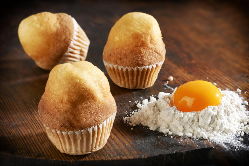 CUPCAKES ON WOODEN TABLE WITH EGG AND FLOUR