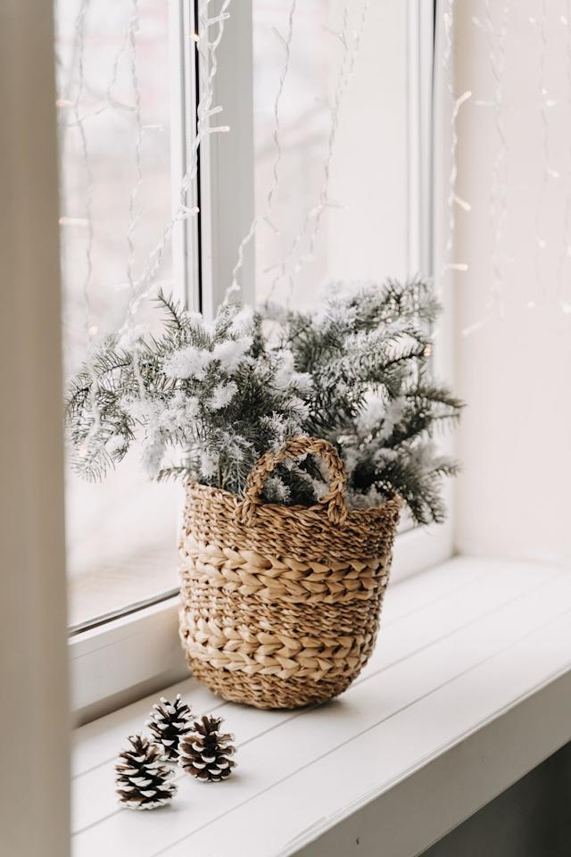 <p>Embrace the beauty of the season by placing a pine tree branch in a simple wicker basket. </p>
