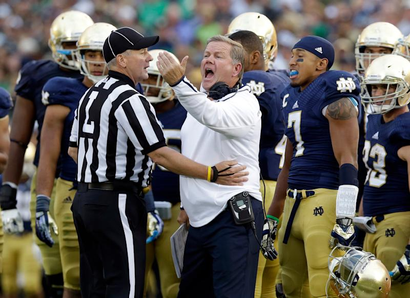Notre Dame head coach Brian Kelly is held back by line judge Paul Engelberts after the bench was called for unsportsmanlike conduct during the second half of an NCAA college football game against Michigan State in South Bend, Ind., Saturday, Sept. 21, 2013. Notre Dame won 17-13. (AP Photo/Michael Conroy)