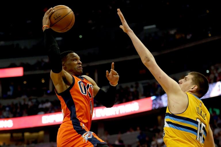 Russell Westbrook of the Oklahoma City Thunder drives to the basket against Nikola Jokic of the Denver Nuggets, at Pepsi Center in Denver, Colorado, on April 9, 2017