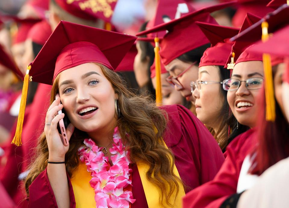 Haley Walters uses her cell phone to locate her mother in the spectator seating area at the Pasadena City College graduation ceremony, June 14, 2019, in Pasadena, California. Walters is five years shy of earning a law degree and, if everything goes according to plan, she should be indebted for $100,000 by the time she enters the workforce. (Photo by Robyn Beck / AFP)