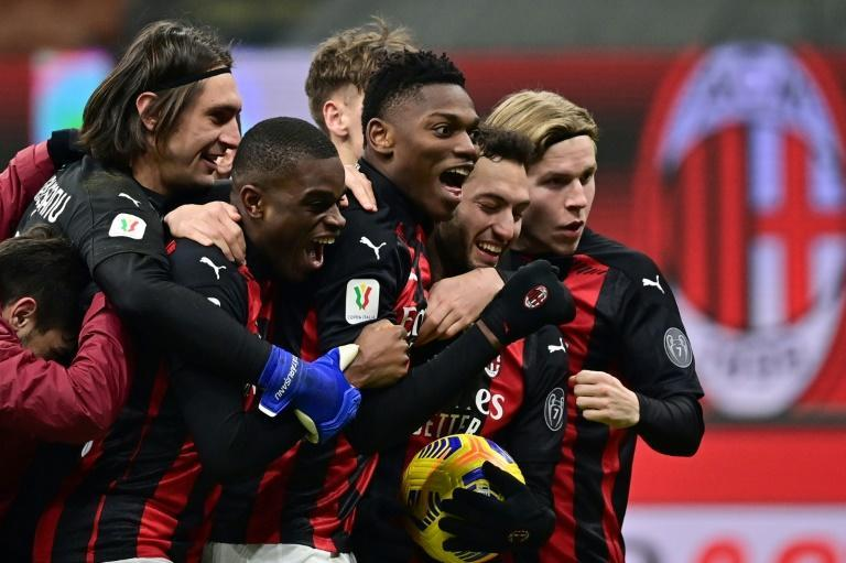 AC Milan players celebrate after Hakan Calhanoglu (2ndR) scored the winner in a penalty shootout against Torino.