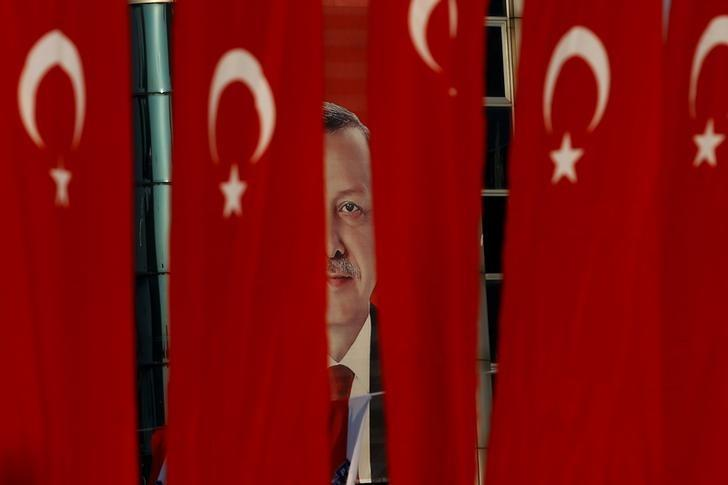 A picture of Turkish President Tayyip Erdogan is seen through Turkish national flags ahead of the constitutional referendum in Istanbul