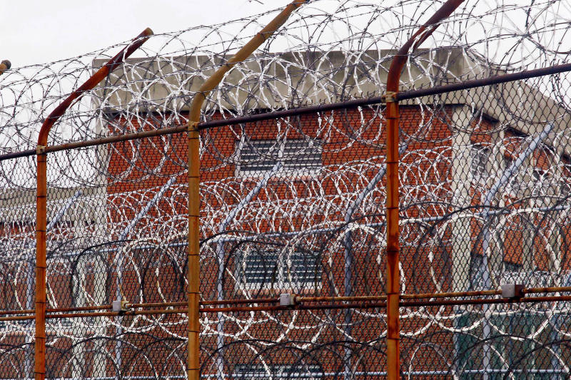 FILE - In this March 16, 2011, file photo, a security fence surrounds inmate housing on the Rikers Island correctional facility in New York. Health experts say prisons and jails are considered a potential epicenter for America's coronavirus pandemic. (AP Photo/Bebeto Matthews, File)