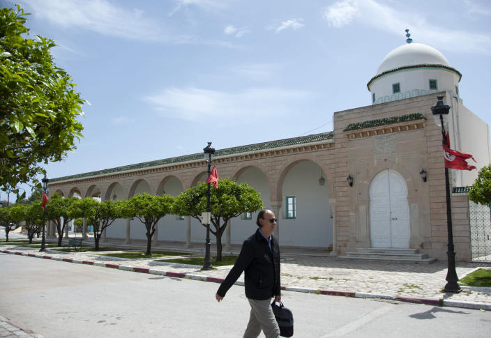 A man walks past a closed mosque in La Marsa district,just outside Tunis, Monday, May, 10, 2021. Tunisia announced on Friday strict new measures to try to contain the spread of the coronavirus, with the prime minister saying that the health system risks collapsing if something is not done. Houses of prayer are being ordered closed starting Sunday for a week, along with outdoor markets and large stores and malls. Shops selling food can remain open. (AP Photo/Hassene Dridi)