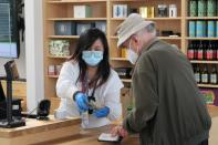 Sales associate Abigail Mationg counts cash during a transaction at a Harborside dispensary in San Leandro
