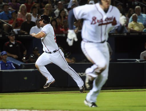 Atlanta Braves' Dan Uggla races home from third to score as Freddie Freeman, right, heads to first, which he reached safely, against the Arizona Diamondbacks during the seventh inning of a baseball game, Tuesday, June 26, 2012, in Atlanta. (AP Photo/John Amis)