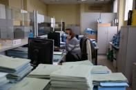 An employee works at a Greek Manpower Employment Organisation (OAED) office near Athens
