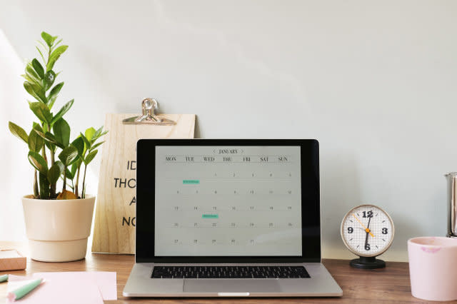Opened laptop with a calendar on desk at home office