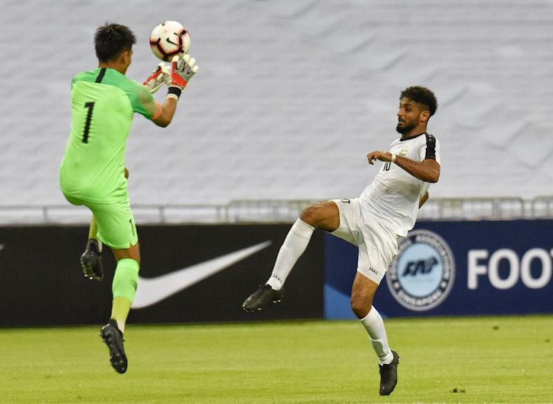 Yemen's Mohsen Mohammed Hasan lobs the ball over Singapore goalkeeper Izwan Mahbud for his side's second goal in their 2022 World Cup qualifying match at the National Stadium (PHOTO: Zainal Yahya/Yahoo News Singapore)