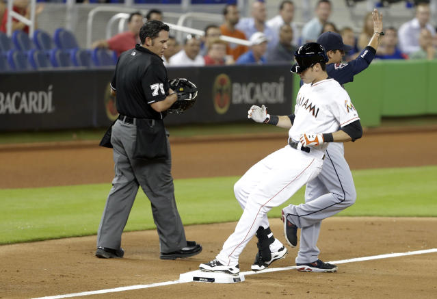 Miami Marlins' Christian Yelich, center, is safe at third with a triple as Atlanta Braves third baseman Ramiro Pena, right, waits for the throw during the third inning of a baseball game, Tuesday, April 29, 2014, in Miami. At left is home plate umpire Manny Gonzalez. (AP Photo)