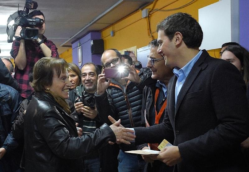 Centre-right party Ciudadanos leader and candidate for general election, Albert Rivera (R) shakes hands with a woman before casting his ballot in L'Hospitalet de Llobregat, near Barcelona on December 20, 2015 (AFP Photo/Lluis Gene)