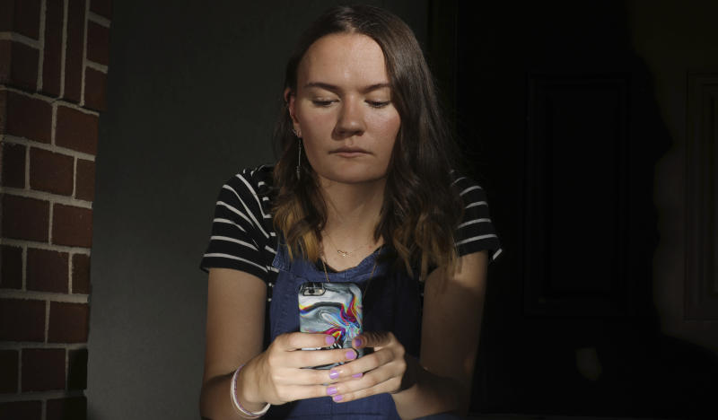 In this Monday, July 22, 2019 photo, Rachel Whalen looks at her phone at her home in Draper, Utah. Whalen remembers feeling gutted in high school when a former friend would mock her online postings, threaten to unfollow or unfriend her on social media and post inside jokes about her to others online. The cyberbullying was so distressing that Whalen even contemplated suicide. There's a rise in cyberbullying nationwide, with three times as many girls reporting being harassed online or by text message than boys, according to the National Center for Education Statistics. (AP Photo/Rick Bowmer)