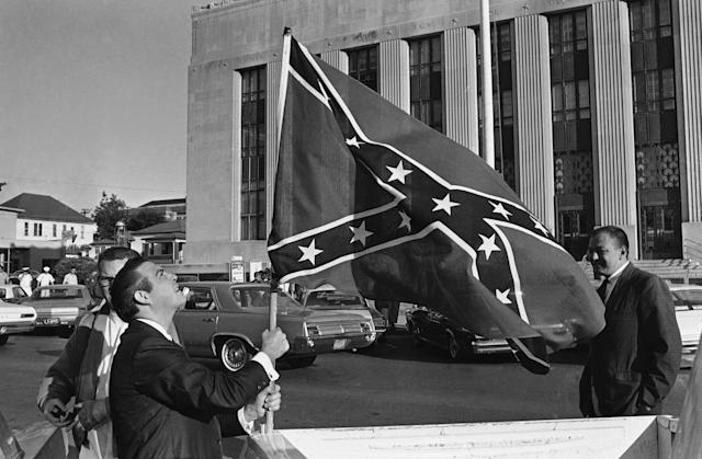 <p>Raymond Roberts (left) raises a large confederate flag on the back of a pickup truck across the street from the federal building in Meridian, Miss. on Monday, Oct. 9, 1967, where his brother Alton Wayne Roberts and 17 others went on trial on conspiracy charges in the 1964 slaying of three civil rights workers. (Photo: AP) </p>