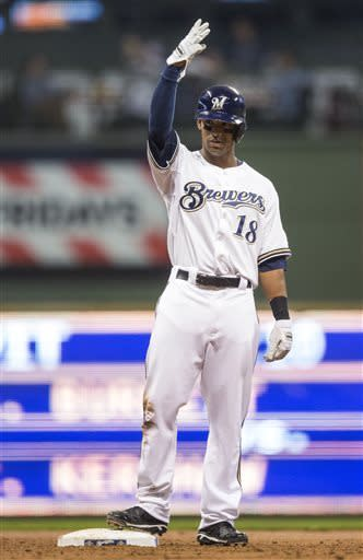 Milwaukee Brewers' Khris Davis holds up his arm after getting his first career hit, against the Arizona Diamondbacks during the second inning of a baseball game Saturday, April 6, 2013, in Milwaukee. (AP Photo/Tom Lynn)