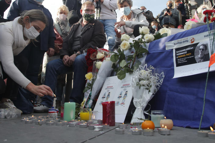 A woman lights a candle on Republique square during a demonstration Sunday Oct. 18, 2020 in Paris. Demonstrations around France have been called in support of freedom of speech and to pay tribute to a French history teacher who was beheaded near Paris after discussing caricatures of Islam's Prophet Muhammad with his class. Samuel Paty was beheaded on Friday by a 18-year-old Moscow-born Chechen refugee who was shot dead by police. (AP Photo/Michel Euler)