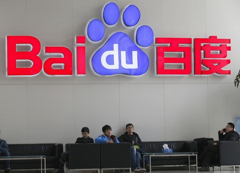 People sit in front of the company logo of Baidu at its headquarters in Beijing