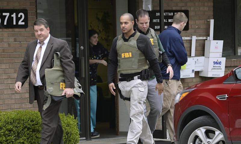 FBI agents leave the office of Dr Fakhruddin Attar at the Burhani clinic in Livonia, Michigan, on Friday after completing a search for documents.