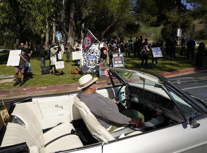FILE - In this Feb. 27, 2021, file photo, a driver in his convertible cruises past a small group of anti-COVID-19 vaccine protesters demonstrating at Elysian Park, outside the Dodger Stadium vaccination mass center in Los Angeles. As the world struggles to break the grip of COVID-19, psychologists and misinformation experts are studying why the pandemic spawned so many conspiracy theories, which have led people to eschew masks, social distancing and vaccines. (AP Photo/Damian Dovarganes, File)