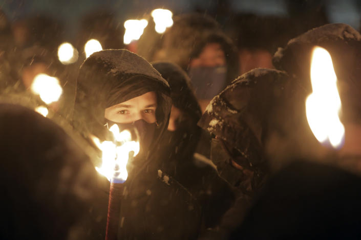 Bulgarian far-right nationalists hold torches as they gathered in the country's capital, to honour a World War II general known for his anti-Semitic and pro-Nazi activities, in Sofia, Saturday, Feb. 13, 2021. Braving sub-zero temperatures, hundreds of dark-clad supporters of the Bulgarian National Union group flocked to a central square where they had planned to kick off the annual Lukov March, a torch-lit procession held every February to the former house of Gen. Hristo Lukov. (AP Photo/Valentina Petrova)