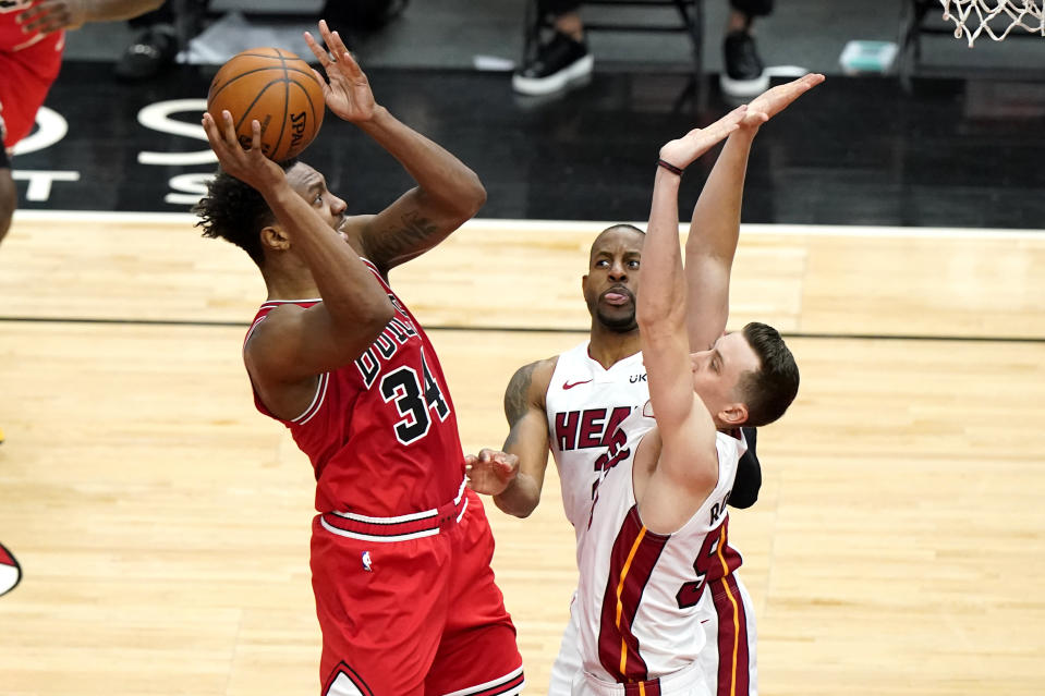 Chicago Bulls center Wendell Carter Jr., left, shoots against Miami Heat forward Andre Iguodala, center, and guard Duncan Robinson during the first half of an NBA basketball game in Chicago, Friday, March 12, 2021. (AP Photo/Nam Y. Huh)