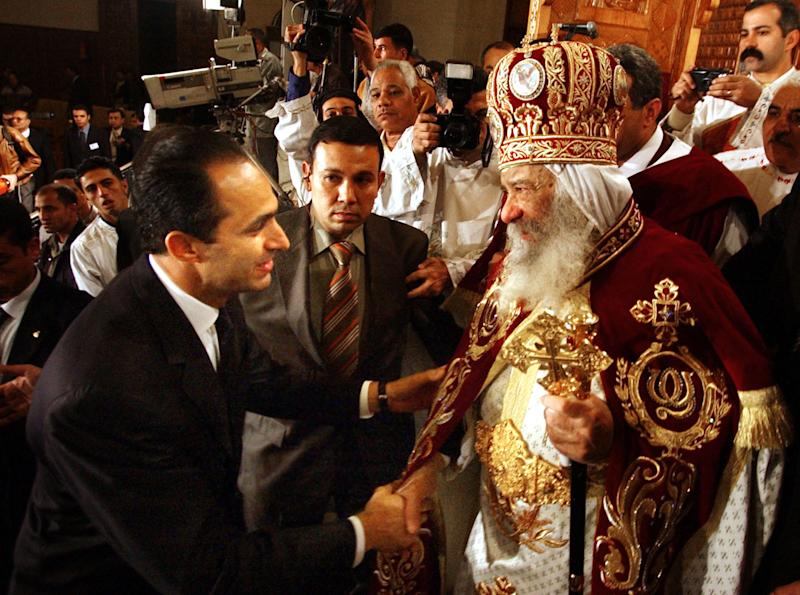 FILE - In this Thursday, Jan. 6, 2005 file photo, Egyptian President Hosni Mubarak's son, Gamal Mubarak, left, congratulates Pope Shenouda III, the head of the Coptic Orthodox Church, marking the Egyptian Christmas which falls on Friday on Egypt's Coptic Christian calendar, after the Pope delivered the sermon at the midnight mass in the Abbassiya cathedral. Pope Shenouda III, the patriarch of the Coptic Orthodox Church who led Egypt's Christian minority for 40 years during a time of increasing tensions with Muslims, has died. He was 88. (AP Photo/Amr Nabil)