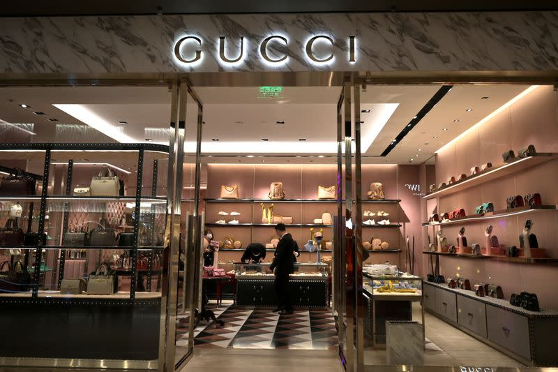 FILE PHOTO: Staff members wearing face masks are seen inside a store of an Italian luxury brand Gucci at a shopping mall, as the country is hit by an outbreak of the novel coronavirus, in Beijing