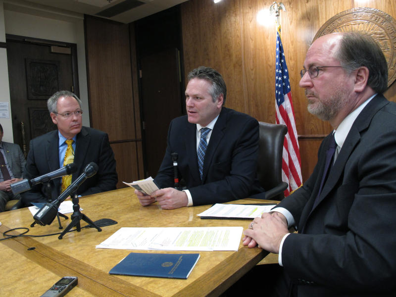 FILE - In this Jan. 30, 2019 file photo, Alaska Gov. Mike Dunleavy, center, speaks to reporters in Juneau, Alaska, with Revenue Commissioner Bruce Tangeman, left, and Attorney General Kevin Clarkson, right. For decades, Alaska has had an uneasy reliance on oil, building budgets around its volatile boom-or-bust nature. When times were rough, prices always seemed to rebound, forestalling a day of reckoning some believe may finally have come. The situation has politicians weighing changes to the annual dividend paid to residents from earnings of the state's oil-wealth fund, the Alaska Permanent Fund. (AP Photo/Becky Bohrer, File)